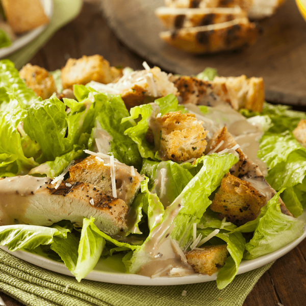 Romaine lettuce with caesar dressing topped with shredded parmesan and croutons