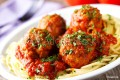 Spaghetti noodles tossed with meatballs in marinara sauce